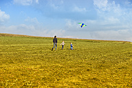 Father with two sons flying kite in meadow - MAEF011636