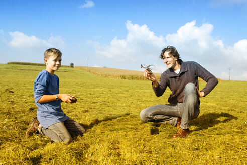 Father and son with remote-controlled helicopter in meadow - MAEF011645