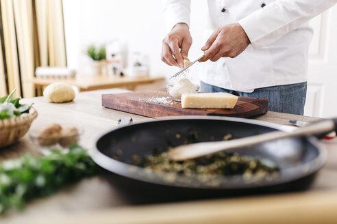 Chef preparing stuffing for ravioli, grating parmesan cheese - JRFF000644