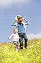 Happy father and daughter walking with doll in meadow - MAEF011648
