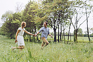Couple in love holding hands while running on a meadow - GIOF000958