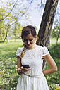 Smiling woman leaning against tree trunk looking at her smartphone - GIOF000978