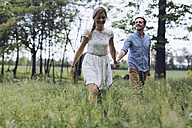Couple in love holding hands while walking on a meadow - GIOF000987