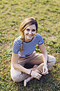 Portrait of smiling blond woman sitting on a meadow - GIOF001002