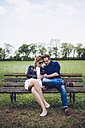 Couple sitting on a bench looking at smartphone - GIOF001005