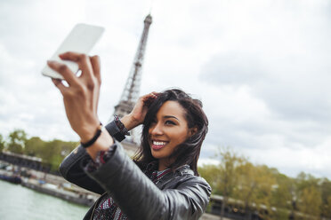 France, Paris, Young woman taking smart phone selfie in front of Eiffel Tower - ZEDF000116