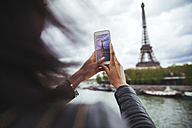 France, Paris, Young woman taking smart phone picture of the Eiffel Tower - ZEDF000119