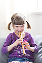 Little girl playing recorder at home - LVF004868