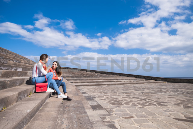Two smiling friends sitting on stairs outdoors - SIPF000456