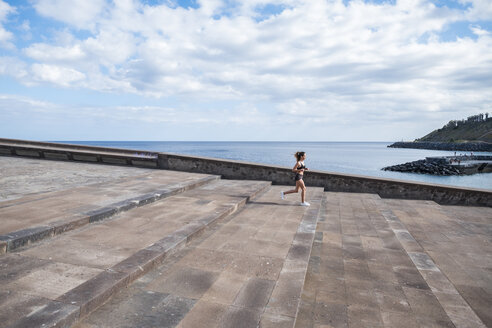 Teenage girl running on stairs at the ocean - SIPF000462