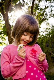 Portrait of little girl holding daisies in her hands - LVF004872