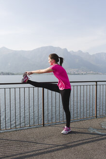 Italy, Lecco, young woman stretching at the lake - MRAF000025