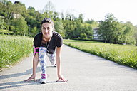 Young woman doing stretching exercises on path in the nature - MRAF000034
