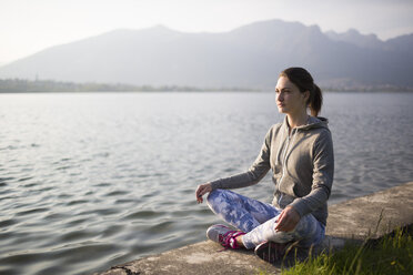 Italy, Lecco, relaxed young woman sitting at the lakeshore - MRAF000040