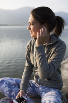 Italy, Lecco, smiling young woman sitting at the lakeshore listening to music - MRAF000046