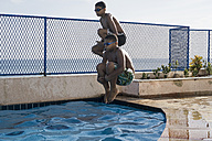 Two boys doing a cannonball dive into swimming pool - MAUF000561