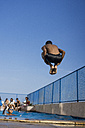 Teenage boy doing a cannonball dive into swimming pool - MAUF000570