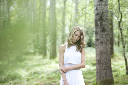 Young woman wearing white dress in the forest - MAE011707