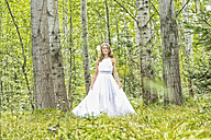 Portrait of young woman wearing white dress in the forest - MAE011710