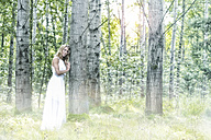 Young woman wearing white dress in the forest - MAE011713