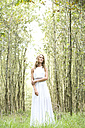 Young woman wearing white dress in the forest - MAE011716