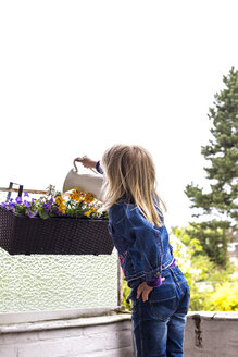 Back view of little girl watering plants on balcony - JFEF000793