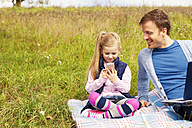 Father and daughter sitting on meadow, smartphone and laptop - MAEF011726