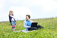 Father and daughter sitting on meadow, laptop, father looking to daughter - MAEF011732