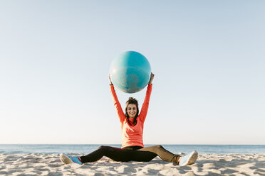 Woman doing sports with gym ball early in the morning on the beach - JRFF000669