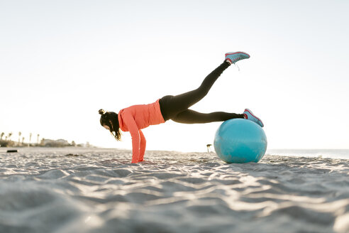 Woman doing sports with gym ball early in the morning on the beach - JRFF000672
