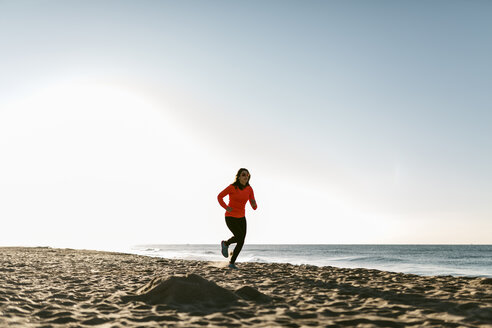 Woman jogging on the beach early in the morning - JRFF000675