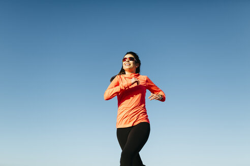 Young woman jogging, blue sky - JRFF000678