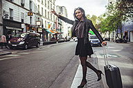 France, Paris, young woman hailing a taxi - ZEDF000123