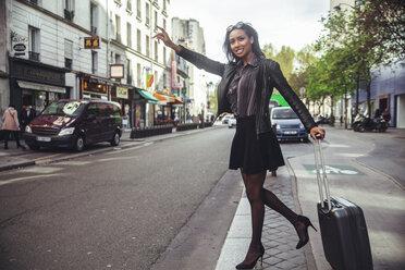 France, Paris, young woman hailing a taxi - ZEDF000123