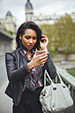 France, Paris, young woman looking at smartphone - ZEDF000129