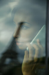 France, Paris, young woman looking through car window while telephoning - ZEDF000135