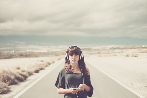 Young woman on the road listening music with headphones - SIPF000472
