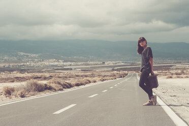 Young woman with suitcase hitchhiking on road - SIPF000481