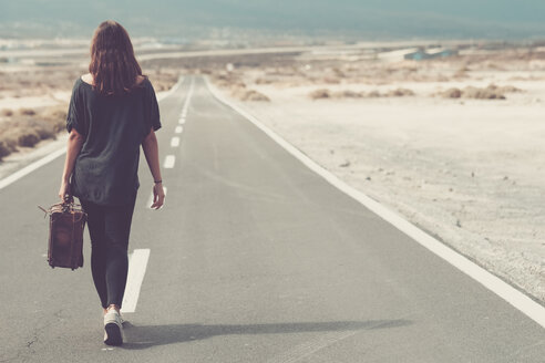 Young woman with suitcase walking on a road - SIPF000484