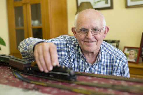 Portrait of smiling senior man with his model railway - RAEF001158