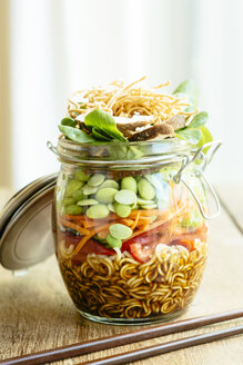 Asian salad in a jar with ramen noodles, red pepper, snow pea pods, carrots, edamame, shiitake mushrooms, salad greens, fried chow mien noodles and dressing - HAWF000899