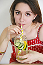 Portrait of woman drinking detox water infused with lemon and cucumber - RTBF000211