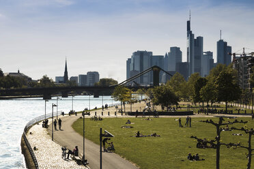 Germany, Hesse, Frankfurt, People at River Main with skyline in background - FCF000943