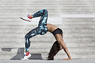 Young woman doing gymnastics at outdoor stairs - ASCF000594