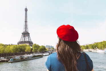 France, Paris, back view of woman wearing red beret looking at Eiffel Tower - GEMF000898