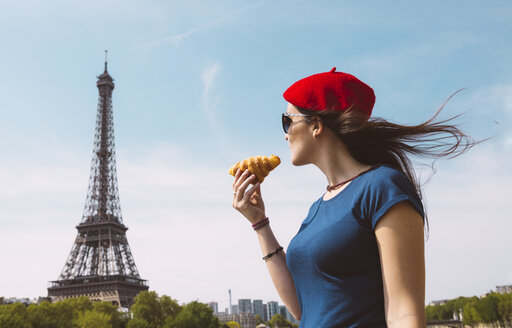 France, Paris, woman holding croissantlooking at Eiffel Tower - GEMF000901