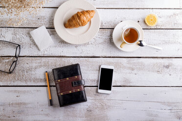 Table with croissant, tea, smart phone and personal organiser - HAPF000354