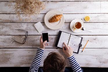 Man working smart phone and personal organiser while having breakfast - HAPF000357