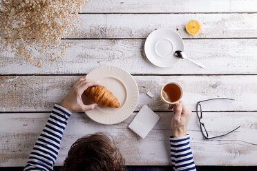 Man sitting at table having tea and a croissant - HAPF000360