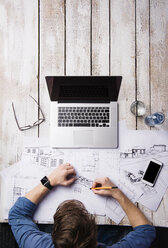 Architect working at desk with laptop, making sketches - HAPF000372